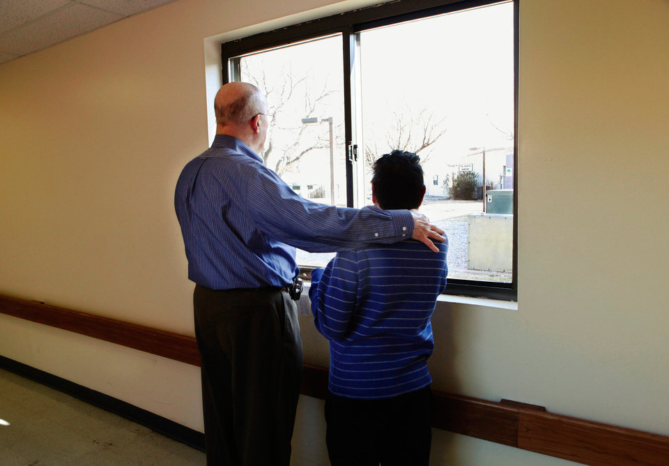 Jim O\'Brien, left, looks out a window with resident Clarence Robinson in a hallway at the Center of Family Love, a group home for mentally disabled people, in Okarche on Monday, Jan. 18, 2010. O\'Brien is the center\'s executive director. Photo by Jim Beckel, The Oklahoman