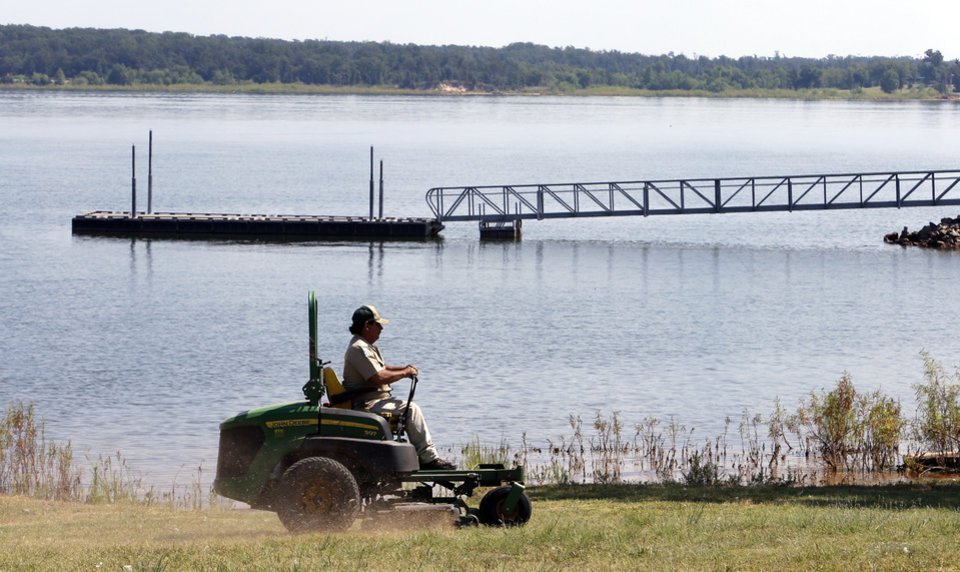 Photo -  Tony Palmer mows Wednesday at Lake Thunderbird State Park in Norman ahead of the Labor Day holiday weekend. Photo by Steve Sisney, The Oklahoman   Steve Sisney -  STEVE SISNEY