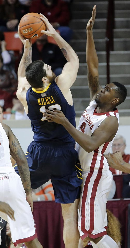 Photo - Oklahoma's Andrew Fitzgerald (4) defends on West Virginia 's Deniz Kilicli (13)  during the first half of the college basketball game between the University of Oklahoma Sooners (OU) and the West Virginia University Mountaineers (WVU) at the Lloyd Noble Center on Wednesday, March 6, 2013, in Norman, Okla. Photo by Chris Landsberger, The Oklahoman