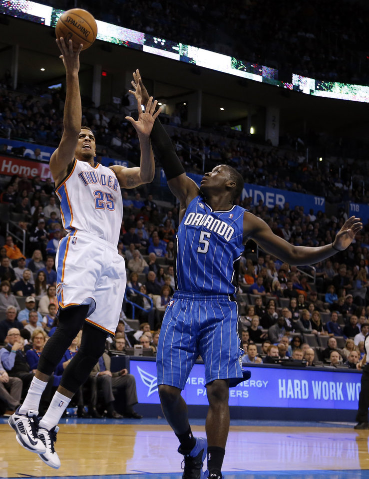 Photo - Oklahoma City's Thabo Sefolosha (25) shoots a basket as Orlando's Victor Oladipo (5) guards during the NBA basketball game between the Oklahoma City Thunder and the Orlando Magic at the Chesapeake Energy Arena, Sunday, Dec. 15,  2013. Photo by Sarah Phipps, The Oklahoman