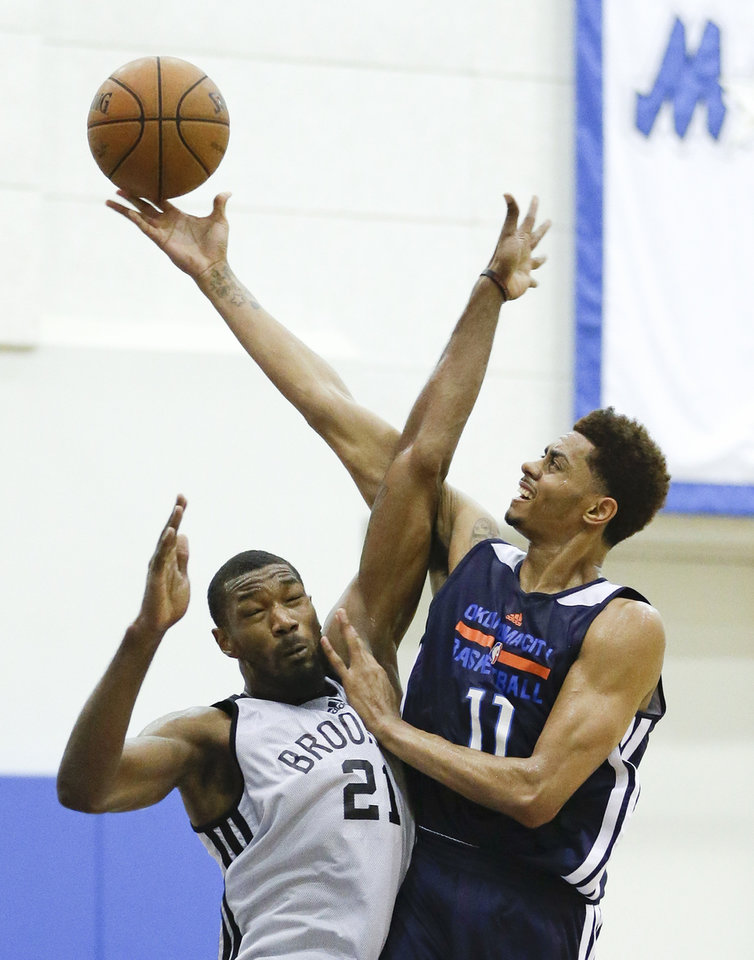 Photo - Oklahoma City Thunder's Jeremy Lamb (11) collides with Brooklyn Nets' Cory Jefferson (21) while going up for a shot during an NBA summer league basketball game in Orlando, Fla., Monday, July 7, 2014. (AP Photo/John Raoux)