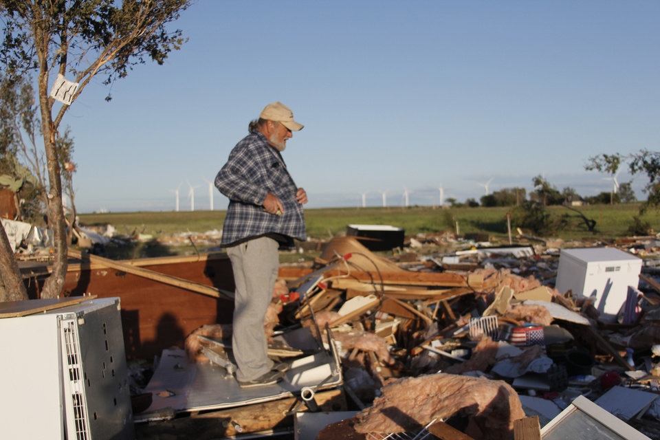 Photo - Rial Allen, who lives in a rural community west of Woodward, walks through what's left of his home Sunday, searching for his wife's eye glasses. Allen lost his son-in-law, Derrin Juul, and his granddaughter, Rosa Marie, 10.  JACLYN COSGROVE/The Oklahoman