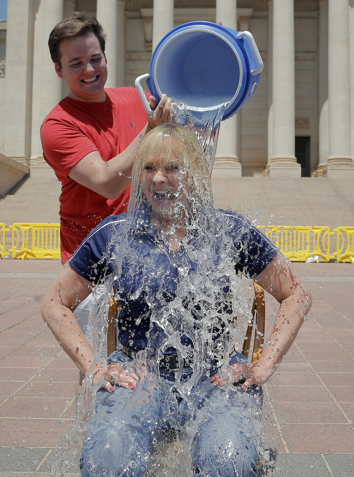 Photo - Gov. Mary Fallin has a bucket of ice water poured on her by her assistant Travis Brauer as Fallin accepts the ALS ice water challenge in front of the south steps of the state capitol in Oklahoma City, Okla. on Tuesday, Aug. 19, 2014.  Photo by Chris Landsberger, The Oklahoman