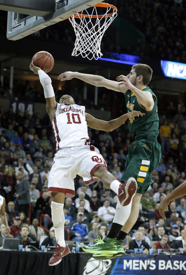 Photo - Oklahoma's Jordan Woodard (10) is fouled by North Dakota State's Taylor Braun (24) during the NCAA men's basketball tournament game between the University of Oklahoma and North Dakota State at the Spokane Arena in Spokane, Wash., Thursday, March 20, 2014. Oklahoma home lost 80-75. Photo by Sarah Phipps, The Oklahoman