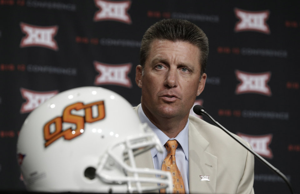 Oklahoma State head coach Mike Gundy speaks to reporters during the NCAA college Big 12 Conference football media days in Dallas, Monday, July 21, 2014. (AP Photo/LM Otero)