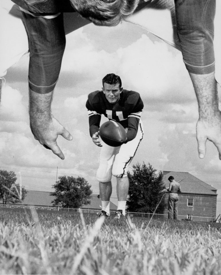 """Ever wonder how it looks from the other side of the line?  Well, here's a defensive lineman's view of Darrell Royal, University of Oklahoma quarterback and punter, about to let fly with a 40-yard boot.  The center is Charley Dowell.  Both of them will face the Texas Aggies when the Sooners renew an old feud at Norman Saturday."" Staff photo by Bob East taken 8/30/48; photo ran in the 10/2/48 Daily Oklahoman. File:  College Football/OU/Darrell Royal/1948"
