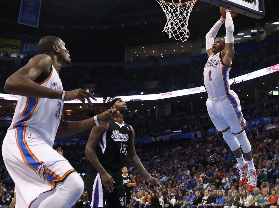 Photo - Oklahoma City Thunder guard Russell Westbrook, right, goes up for a dunk in front of Sacramento Kings center DeMarcus Cousins (15) and Thunder's Kevin Durant (35) during the third quarter of an NBA basketball game in Oklahoma City, Friday, March 28, 2014. Oklahoma City won 94-81. (AP Photo/Sue Ogrocki)
