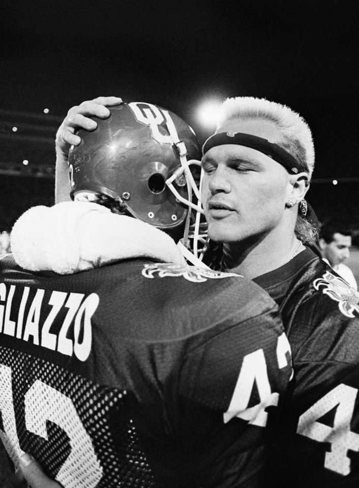 OU\'s Brian Bosworth hugs a teammate before kickoff of the 1987 Orange Bowl vs. Arkansas. Bosworth did not play because he was barred when it was discovered he had steriods in his system. AP ARCHIVE PHOTO