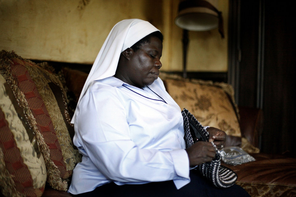 Sister Rosemary Nyirumbe sews a strap onto a pop-tab purse Tuesday at the home of Reggie and Rachelle Whitten of Oklahoma City.  <strong>SARAH PHIPPS - SARAH PHIPPS</strong>
