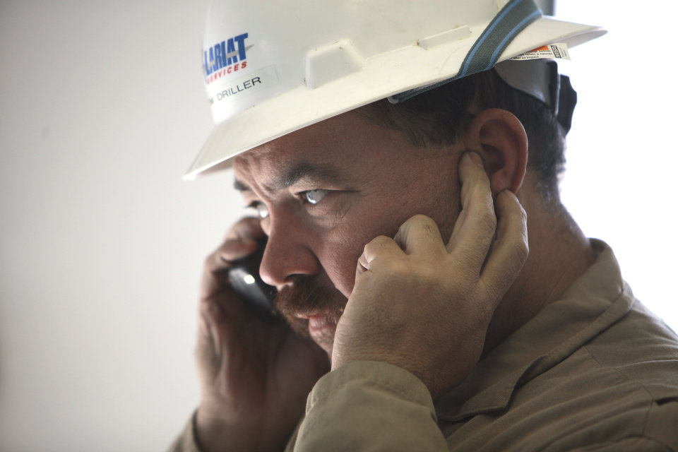 Driller Tim Lovell covers an ear so as he talks on the phone in the Top Dog House at a SandRidge oil drilling rig near Medford, Thursday, October 18, 2012. This is for Oklahoma Inc. Photo By David McDaniel/The Oklahoman