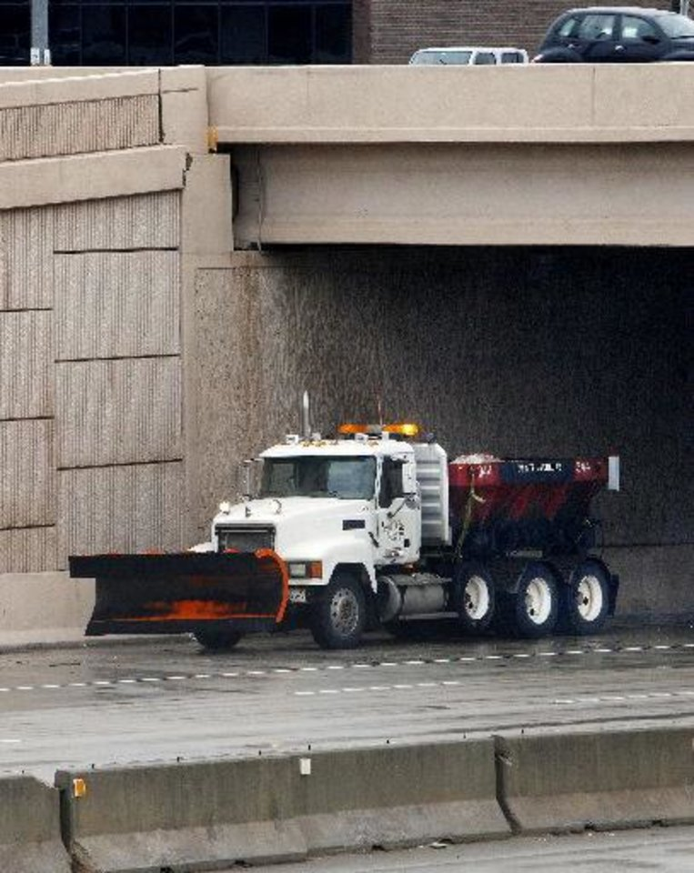 Photo - Snow plows stage under the NE 63 bridge on Broadway Extension on Monday in Oklahoma City. Photo by Paul B. Southerland, The Oklahoman