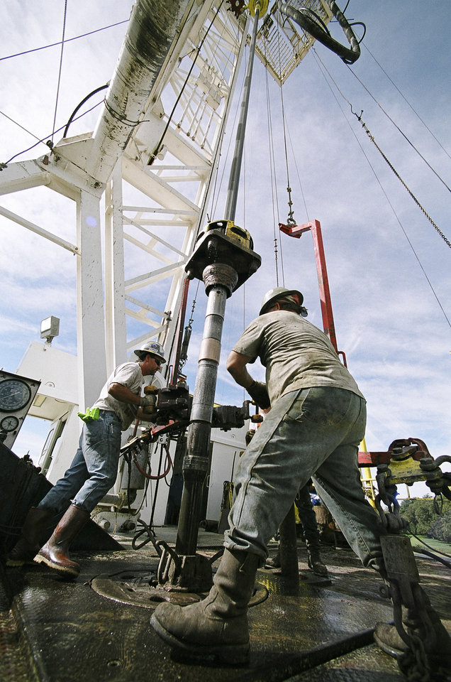 Photo - Workers change drilling pipe on a Chesapeake Energy Corp. rig near Marlow in this file photo from 2004. Photo by Steve Sisney, The Oklahoman Archives