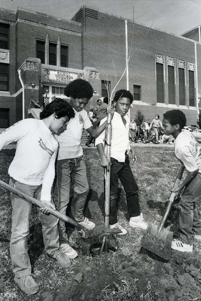 Photo - Students, from left, Sergio Hernandez, James David, Cornelius Peoples and Derrick Smith plant a tree at the school in 1986.  David McDaniel