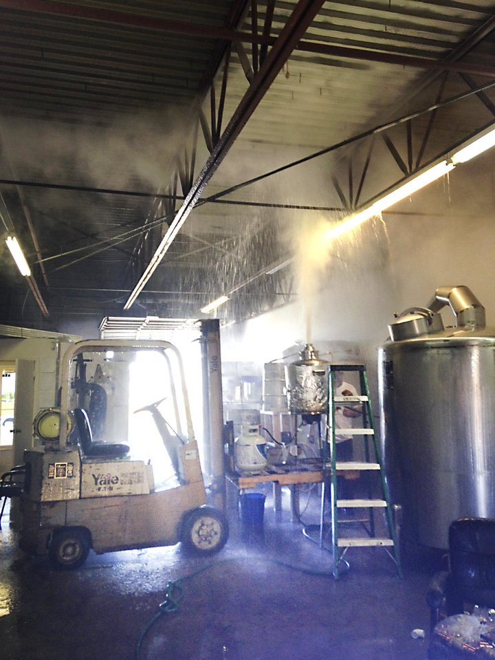Photo - Vodka spews from a distilling tank at Success Vodka Distiller in Moore, Friday, June 13, 2014. Jeff Thurmon, who was injured in the accident, is standing behind the ladder. Photo by Brianna Bailey, The Oklahoman