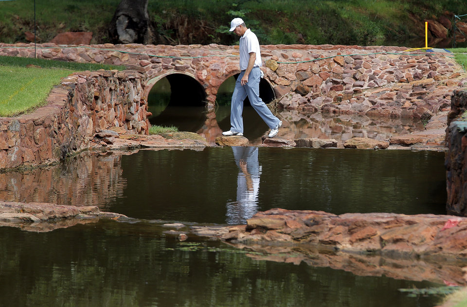 Photo - Bob Tway crosses the bridge from the fourth green to the fifth tee during practice rounds for the U.S. Senior Open golf tournament at Oak Tree National in Edmond, Okla. on Wednesday, July 9, 2014. Photo by Chris Landsberger, The Oklahoman