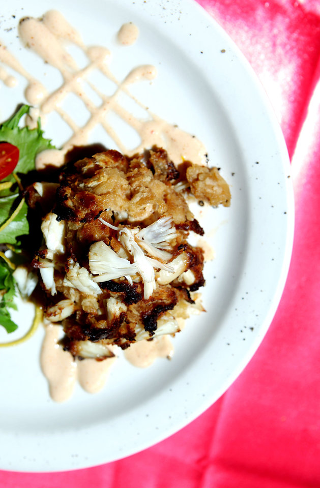 Photo - Crab cakes at Rococo are served with Thai-infused dressing, and wild field greens.  John Clanton - The Oklahoman