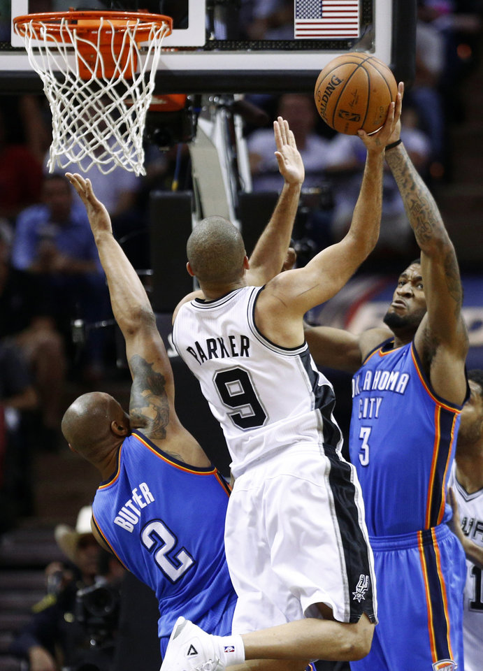 Photo - San Antonio's Tony Parker (9) goes to the basket between Oklahoma City's Caron Butler (2) and Perry Jones (3) during Game 2 of the Western Conference Finals in the NBA playoffs between the Oklahoma City Thunder and the San Antonio Spurs at the AT&T Center in San Antonio, Wednesday, May 21, 2014. Photo by Sarah Phipps, The Oklahoman