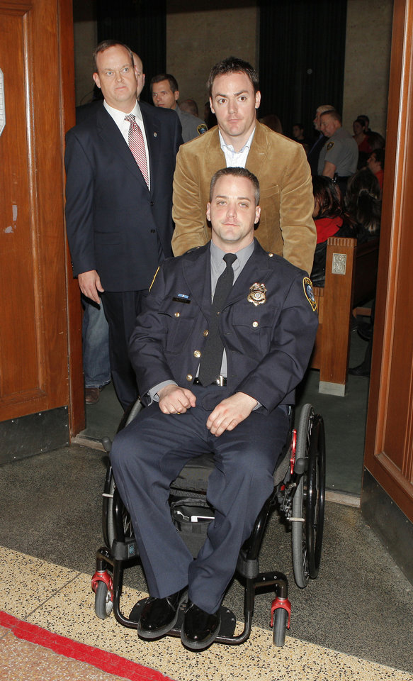 Photo - Oklahoma City police officer Chad Peery — in a wheelchair being pushed by his brother, Mark Peery — leaves the courtroom Jan. 27, 2012, after the sentencing of Cadmio Lopez at the Oklahoma County Courthouse in Oklahoma City.  Photo by Paul B. Southerland, The Oklahoman Archives