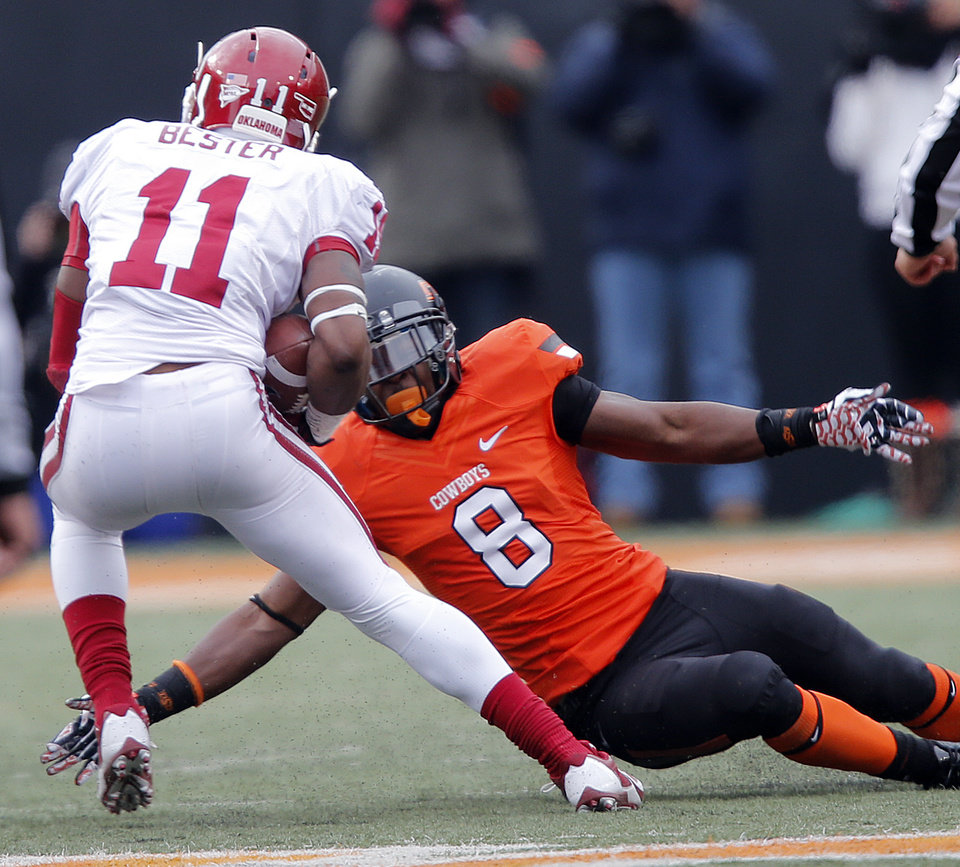 Photo - Oklahoma's Lacoltan Bester (11) cuts back on a tackle attempt by Oklahoma State's Daytawion Lowe (8) during the Bedlam college football game between the Oklahoma State University Cowboys (OSU) and the University of Oklahoma Sooners (OU) at Boone Pickens Stadium in Stillwater, Okla., Saturday, Dec. 7, 2013. Photo by Chris Landsberger, The Oklahoman