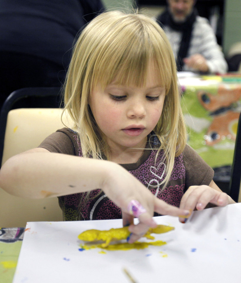 Kayla Duncan, 4, rolls paint from a plastic lizard onto paper.