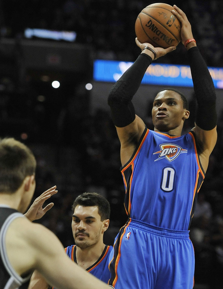 Photo - Oklahoma City Thunder guard Russell Westbrook (0) shoots against San Antonio Spurs forward Aron Baynes, left, of Australia, during the second half of an NBA basketball game, Thursday, Dec. 25, 2014, in San Antonio. Oklahoma City won 114-106. (AP Photo/Darren Abate)