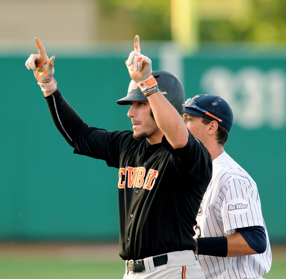 Photo - Oklahoma State first baseman Tanner Krietemeier, left, celebrates in front of Cal State Fullerton second baseman Timmy Richards, upon reaching second base on a double in the 3rd inning of an NCAA college baseball regional tournament game in Stillwater, OK, Saturday, May 31, 2014. (AP Photo/Brody Schmidt)
