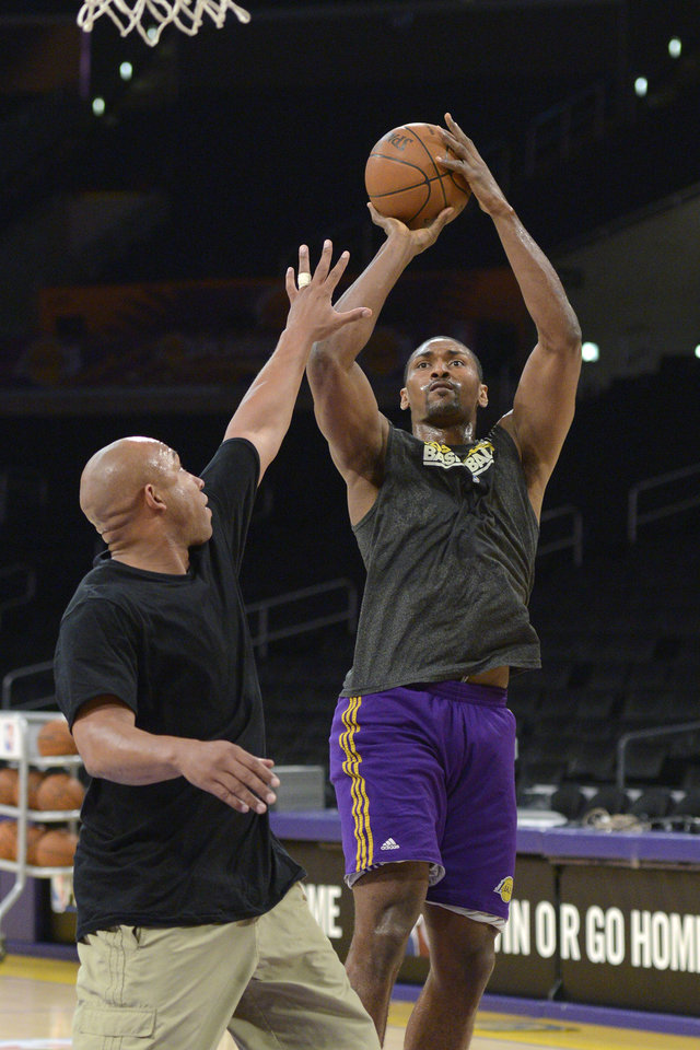 Photo - Los Angeles Lakers small forward Metta World Peace, right, works out with a trainer prior to Game 5 of an NBA first-round playoff basketball game against the Denver Nuggets, Tuesday, May 8, 2012, in Los Angeles. Metta World Peace is still serving a seven-game suspension his elbow to the head of James Harden in an April 22 game against the Oklahoma City Thunder. (AP Photo/Mark J. Terrill)  ORG XMIT: LAS101