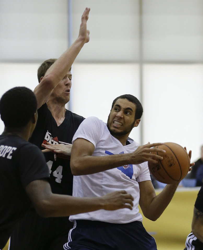 Oklahoma City Thunder's Grant Jerrett, right, looks for an open shot over Detroit Pistons' Travis Peterson (44) and Kentavious Caldwell-Pope, left, during an NBA summer league basketball game, Tuesday, July 9, 2013, in Orlando, Fla. (AP Photo/John Raoux) ORG XMIT: DOA111