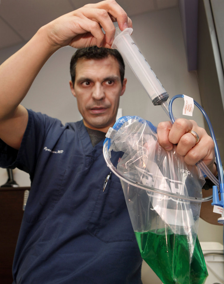 """Photo - Dr. Ryan Brown, emergency room physician at  Children's Hospital, demonstrates the technique for performing a gastric lavage, commonly referred to  as """"pumping the stomach.""""  Photo by Jim Beckel, The Oklahoman"""