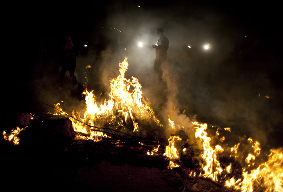 Photo - Egyptian activist walk by burning tires during an anti-Muslim Brotherhood protest in front of the Brotherhood's headquarters, in Cairo, Egypt, Sunday, March 17, 2013. Egypt is mired in another of the wave after wave of protests, clashes and unrest that have plagued the country since the ouster of authoritarian leader Hosni Mubarak in the pro-democracy uprising two years ago. (AP Photo/Nasser Nasser)