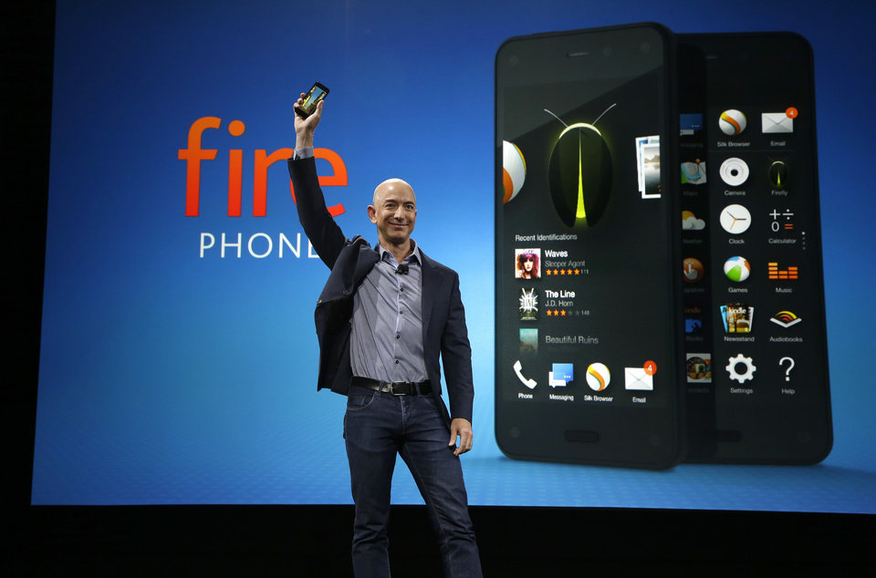 Photo - Amazon CEO Jeff Bezos holds up the new Amazon Fire Phone at a launch event, Wednesday, June 18, 2014, in Seattle. (AP Photo/Ted S. Warren)