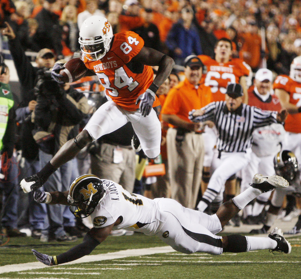Photo - Hubert Anyiam leaps over Kenji Jackson in the first quarter during the college football game between Oklahoma State University (OSU) and the University of Missouri (MU) at Boone Pickens Stadium in Stillwater, Okla. Saturday, Oct. 17, 2009.  Photo by Sarah Phipps, The Oklahoman