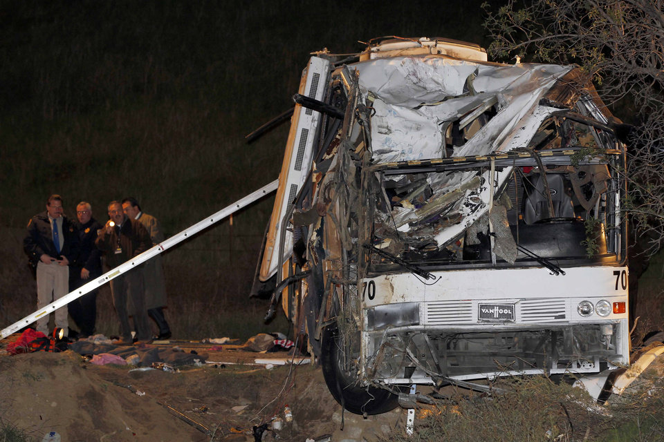 Photo - Investigators continue working the scene where at least eight people were killed and 38 people were injured after a tour bus carrying Mexican tourists careened out of control while traveling down a mountain road, struck a car, flipped and plowed into a pickup truck, near Yucaipa, Calif., Sunday, Feb. 3, 2013. (AP Photo/Nick Ut)