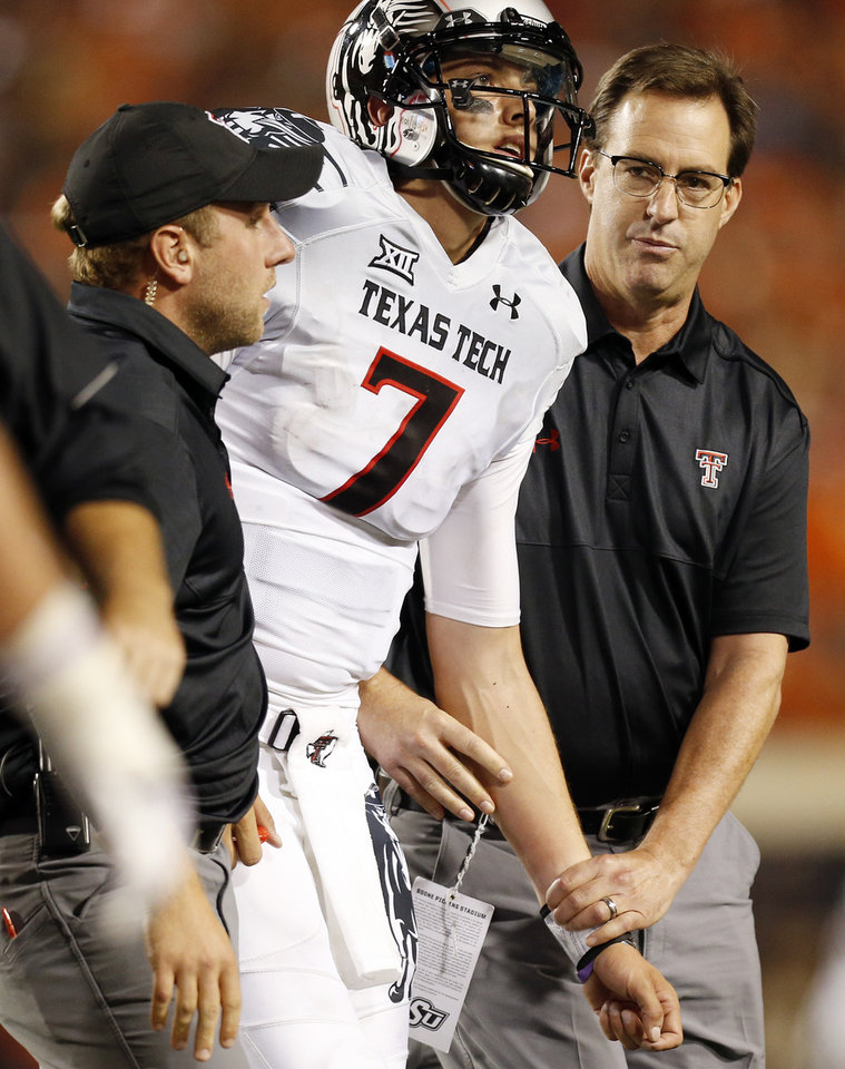 Photo - Texas Tech quarterback Davis Webb (7) leaves the field after being injured in the fourth quarter during a college football game between the Oklahoma State Cowboys (OSU) and the Texas Tech Red Raiders at Boone Pickens Stadium in Stillwater, Okla., Thursday, Sept. 25, 2014. OSU won, 45-35. Photo by Nate Billings, The Oklahoman