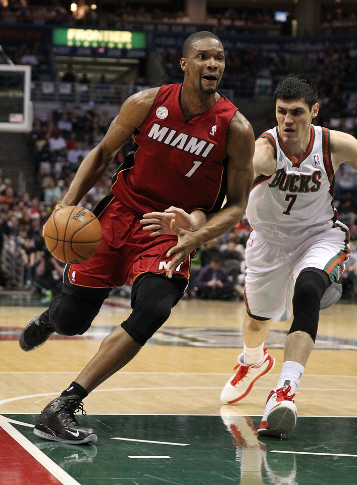 Miami Heat center Chris Bosh (1) drives to the basket as Milwaukee Bucks forward Ersan Ilyasova (7), of Turkey, defends in the first quarter during Game 4 of their first-round NBA basketball playoff series, Sunday, April 28, 2013, in Milwaukee. (AP Photo/The Miami Herald, Al Diaz) MAGS OUT.