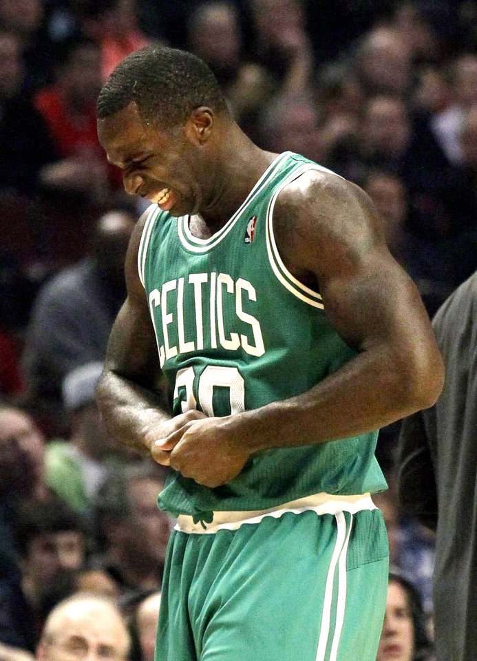 Boston Celtics forward Brandon Bass holds his hand in pain during the first half of an NBA basketball game against the Chicago Bulls, Monday, Nov. 12, 2012, in Chicago. (AP Photo/Charles Rex Arbogast)