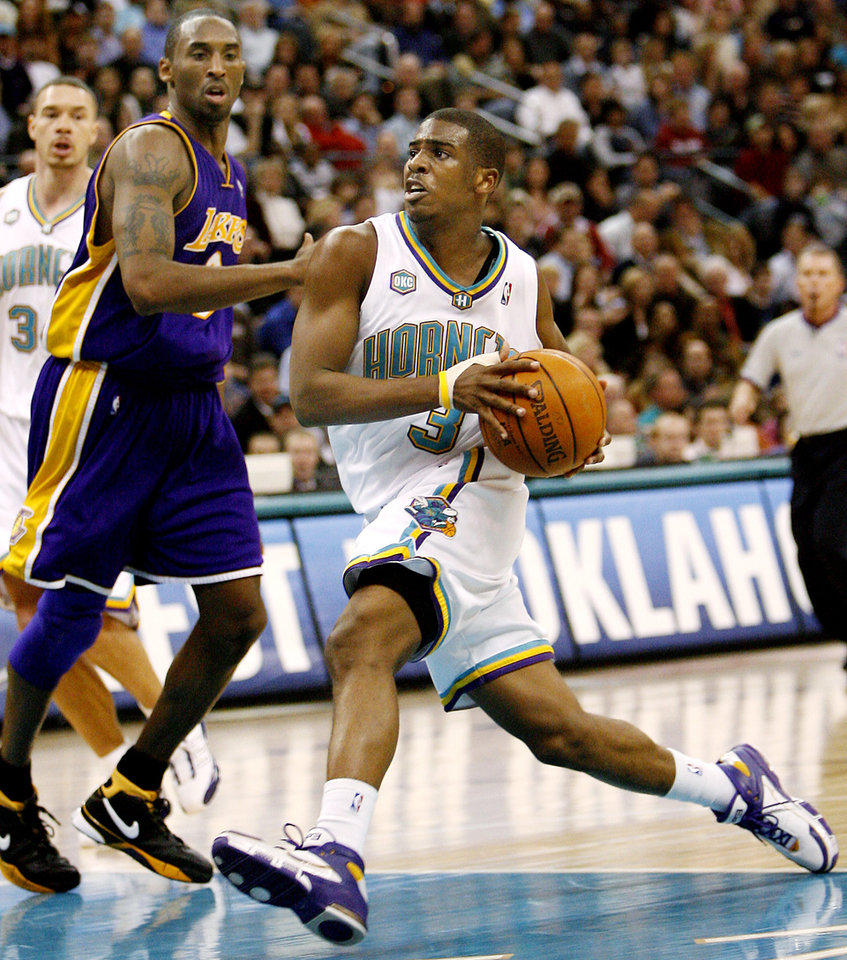 Photo - New Orleans Hornets guard Chris Paul (3) drives the ball past Los Angeles Lakers guard Kobe Bryant (8) in the second half of Saturday night's NBA basketball game Feb. 4, 2006 in Oklahoma City. Hornets won 106-90. (AP Photo/Ty Russell)