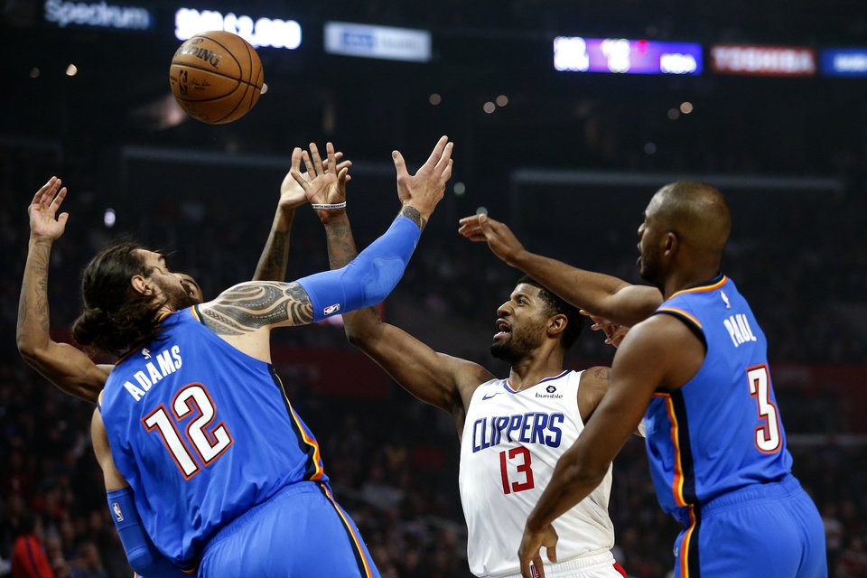 Photo - Los Angeles Clippers' Paul George (13) shoots under pressure from Oklahoma City Thunder's Steven Adams (12) and Chris Paul (3) during the first half of an NBA basketball game, Monday, Nov. 18, 2019, in Los Angeles. (AP Photo/Ringo H.W. Chiu)