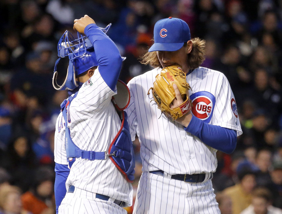 Photo - Chicago Cubs starting pitcher Jeff Samardzija, right, talks to catcher Welington Castillo during the fourth inning of an interleague baseball game against the Chicago White Sox Monday, May 5, 2014, in Chicago. (AP Photo/Charles Rex Arbogast)