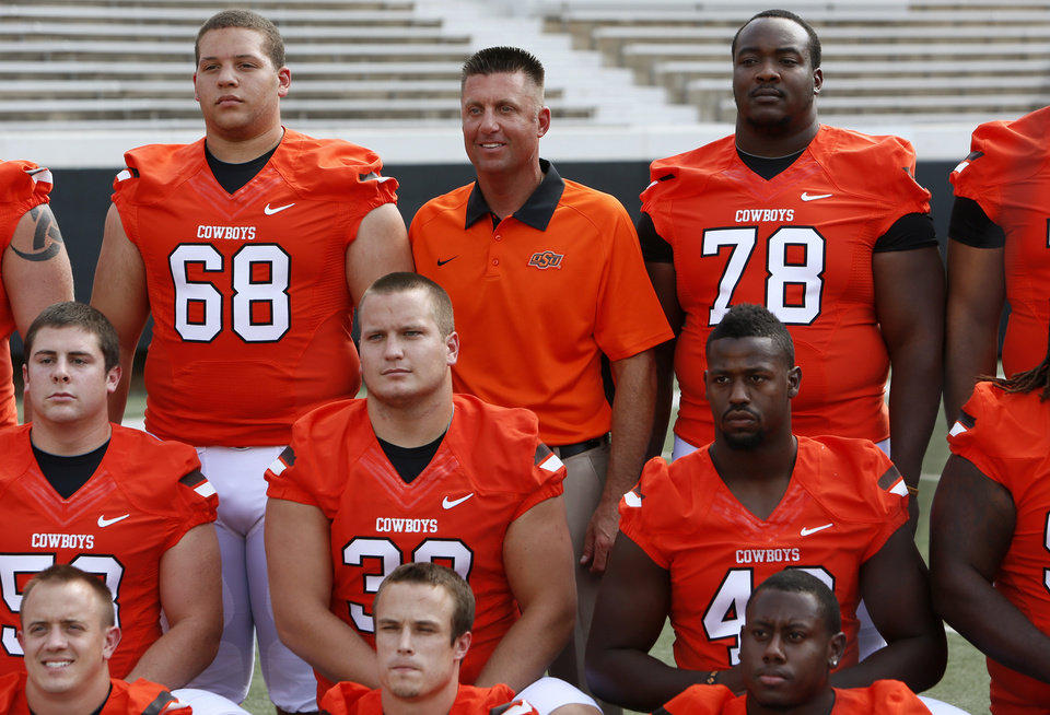 Photo - OSU head football coach Mike Gundy poses with the team's seniors during media day for the OSU football team at Gallagher-Iba Arena in Stillwater, Okla., Saturday, Aug. 4, 2012. Photo by Nate Billings, The Oklahoman