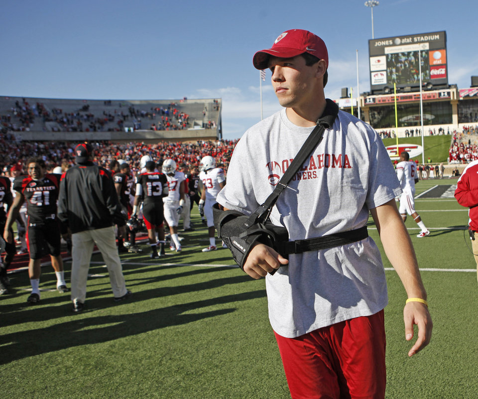 Photo - OU's Sam Bradford leaves the field after OU's 41-13 loss in the college football game between the University of Oklahoma Sooners (OU) and Texas Tech University Red Raiders (TTU ) at Jones AT&T Stadium in Lubbock Okla., Saturday, Nov. 21, 2009. Photo by Bryan Terry, The Oklahoman