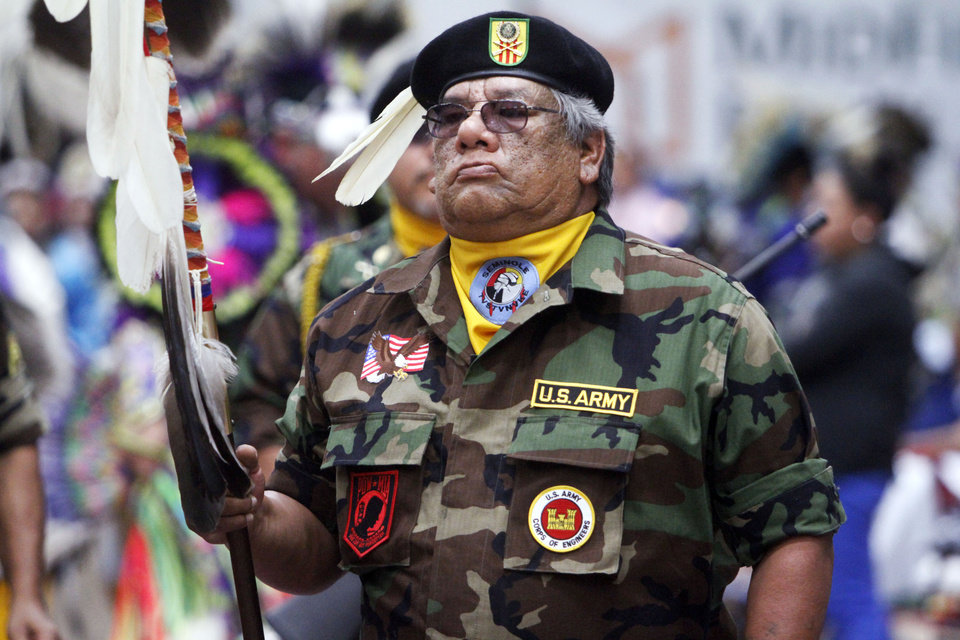 Photo -  Alex Fish, holding the eagle staff, leads the Seminole Nation Honor Guard in the grand entrance. Photo by K.T. King, The Oklahoman   KT King -