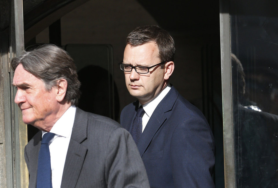 Photo - Andy Coulson, background, former News of the World editor leaves the Central Criminal Court in London, Tuesday, June 24, 2014. Coulson was convicted of phone hacking Tuesday, but fellow editor Rebekah Brooks was acquitted after a  trial centering on illegal activity at the heart of Rupert Murdoch's newspaper empire. A jury at London's Old Bailey unanimously found Coulson, the former spin doctor of British Prime Minister David Cameron, guilty of conspiring to intercept communications. Brooks was acquitted of that charge and of counts of bribing officials and obstructing police. The nearly eight-month trial was triggered by revelations that for years the News of the World used illegal eavesdropping to get stories, listening in on the voicemails of celebrities, politicians and even crime victims. (AP Photo/Lefteris Pitarakis)