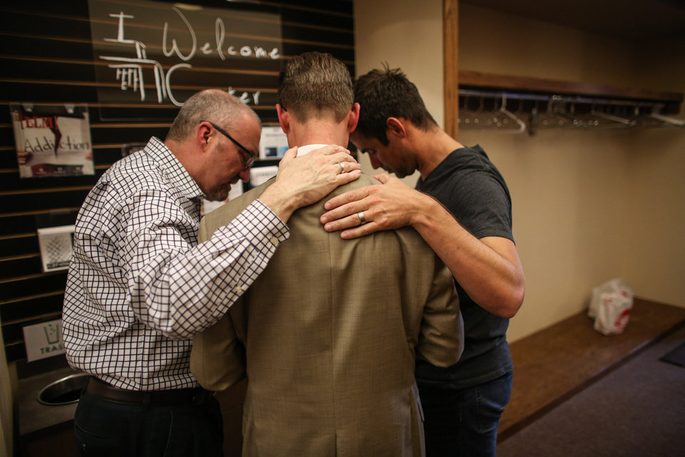 Photo - SPU President Dan Martin, center, prays with university trustee Matt Whitehead and Geoff Smith, right, in the Free Methodist church after a shooting at Seattle Pacific University on Thursday, June 5, 2014. A man that shot students was disarmed by others at the scene.  (AP Photo/seattlepi.com, Joshua Trujillo)