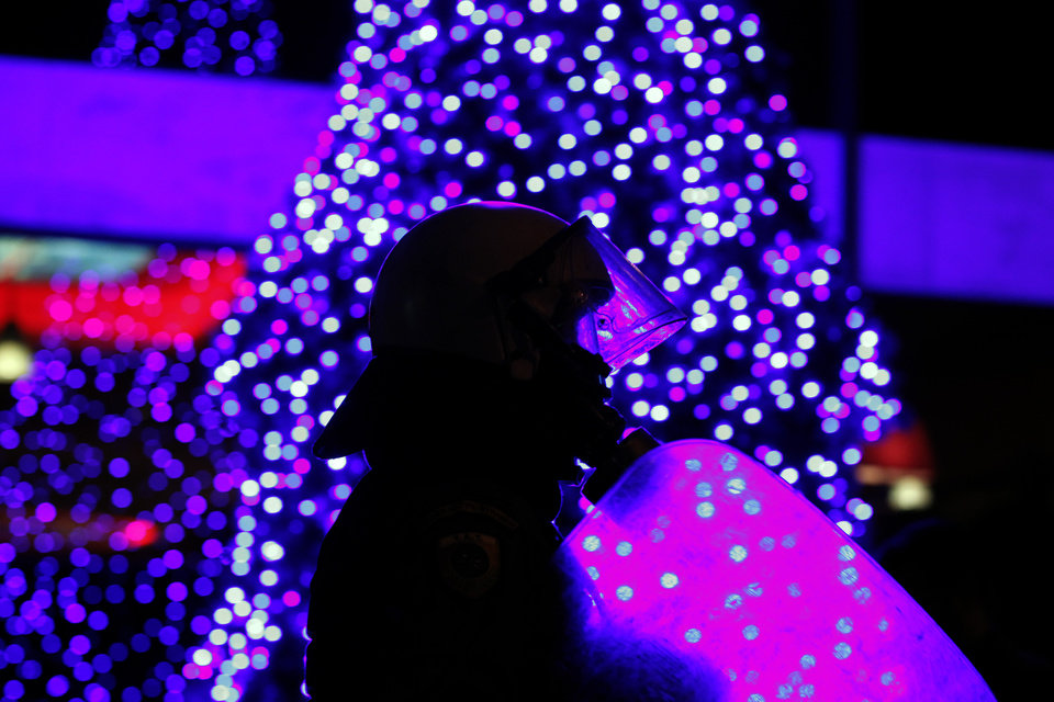 A riot policeman walks by a Christmas tree during a rally in Athens on Saturday, Nov. 17, 2012. Several thousand marchers are commemorating the 39th anniversary of a deadly student uprising against the then ruling dictatorship, with more than 6,000 police deployed in the center of the Greek capital. (AP Photo/Kostas Tsironis)