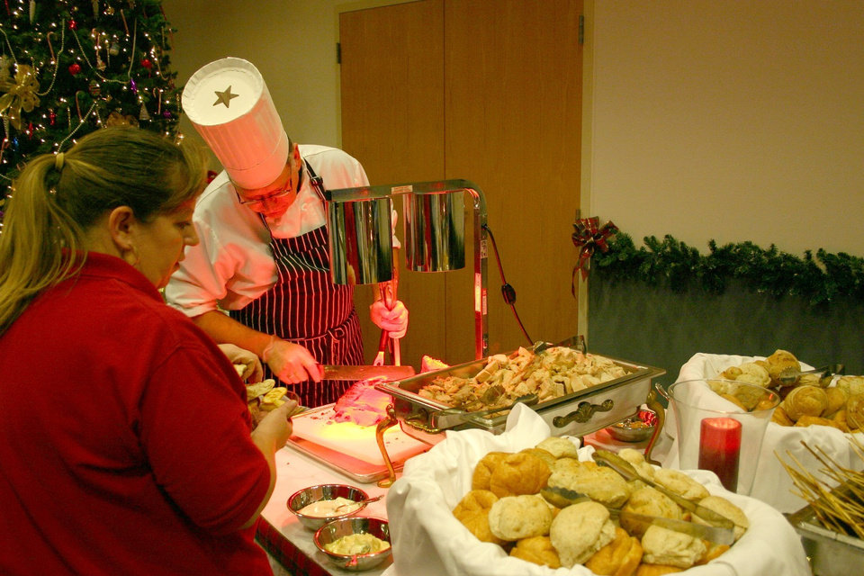 Gaylan Oliver, executive chef for the J. D. McCarty Center's conference facility, slices roast beef for McCarty Center employee Cheryl Sosa during the 40 et 8's 59th annual Christmas party for invited guests, inpatients and staff. Approximately 250 people attended this year. A smaller attendance of this year's event was attributed to the ice storm earlier in the week and the lingering power outages in some areas.<br/><b>Community Photo By:</b> Greg Gaston<br/><b>Submitted By:</b> Greg, Norman