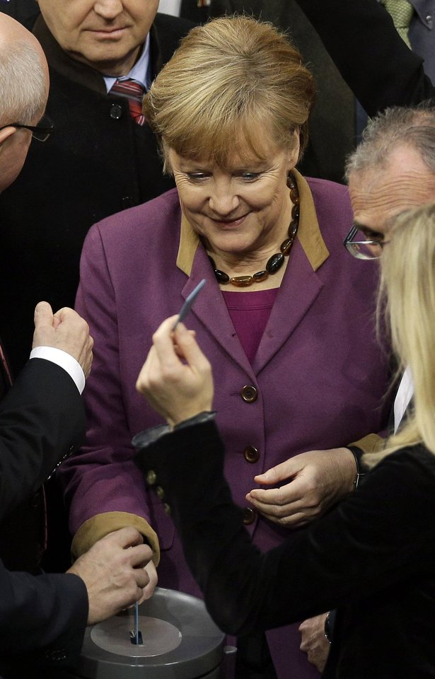 Photo - FILE - In this Nov. 30, 2012 file picture German Chancellor Angela Merkel casts her vote at the German federal parliament, Bundestag, in Berlin, Germany.  The German Parliament has given its overwhelming backing to a deal aimed at trimming Greece's debt load and keeping the country financially afloat. Lawmakers voted 473-100 on Friday to back the complex deal reached by European finance ministers earlier this week.  Germany's chancellor says in an interview published saturday Dec. 1, 2012  she understands the frustration felt by many Germans over the repeated bailout programs for Greece.  But Angela Merkel also insists that helping debt-ridden Greece is in her country's self-interest because it helps stabilize the 17-nation eurozone on which Germany's prosperity depends.  (AP Photo/Michael Sohn, File)