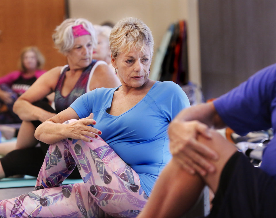 Photo -  Merradyth McAllister, shown here, and her husband Jack McAllister participate in a yoga class at the MAPS 3 Health and Wellness Center near NW 122 and Rockwell Avenue. [Photo by Jim Beckel, The Oklahoman]