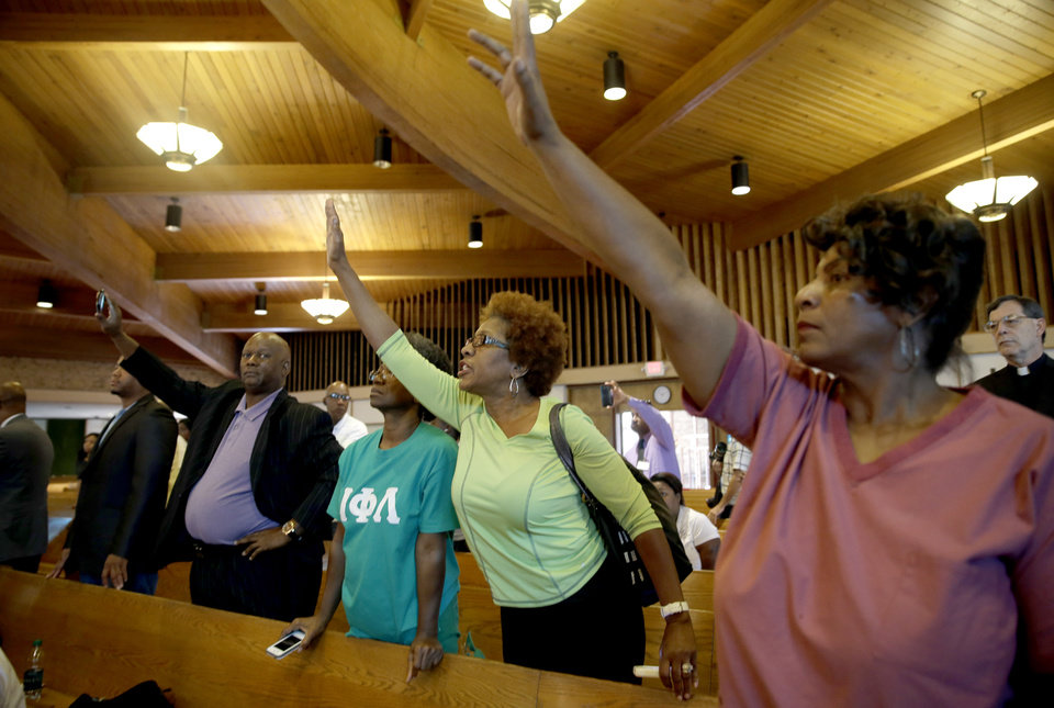 Photo - Residents attempt to ask questions during a news conference held to discuss preliminary results of a second autopsy done on 18-year-old Michael Brown Monday, Aug. 18, 2014, in St. Louis County, Mo. The independent autopsy shows Brown was shot at least six times. (AP Photo/Jeff Roberson)