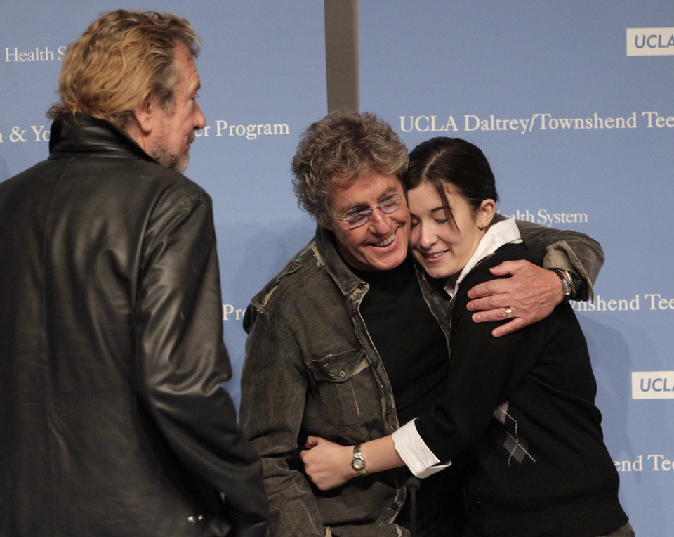 Roger Daltrey, center, a member of the British rock band The Who, hugs 17-year-old cancer survivor Sarah Sterner as Robert Plant of Led Zeppelin, left, watches after a news conference at the Ronald Reagan UCLA Medical Center in Los Angeles, Friday, Nov. 4, 2011. Daltrey and Plant pledged to raise money to renovate part of the hospital pediatric floor into a separate space for patients ages 15 to 25. (AP Photo/Jae C. Hong)